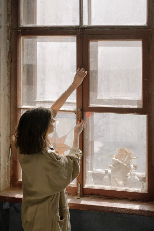 Woman in White Shirt Looking Out the Window