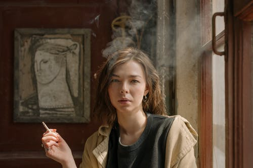 Woman in Black Crew Neck Shirt and Brown Coat Holding Cigarette Stick