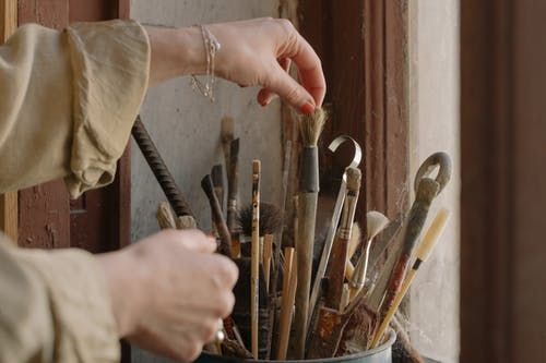 Person Holding Brown Wooden Handle Paint Brush