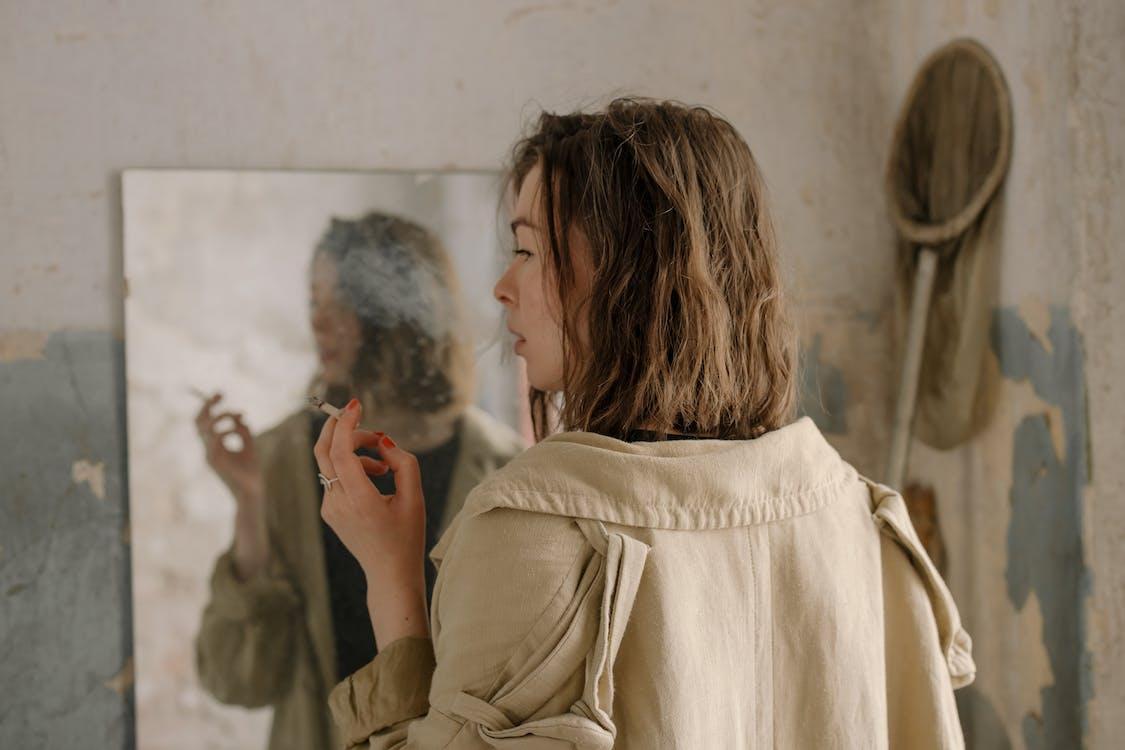 Woman in Beige Coat Holding Her Hair
