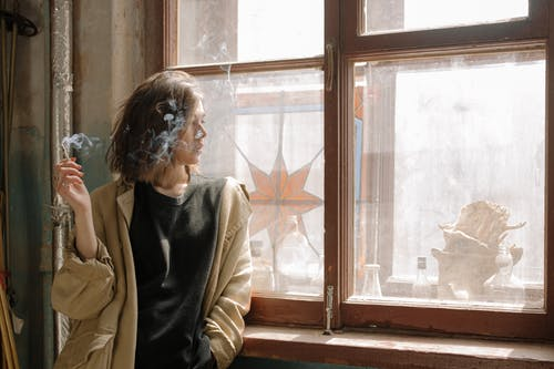 Woman in Black Coat Sitting by the Window