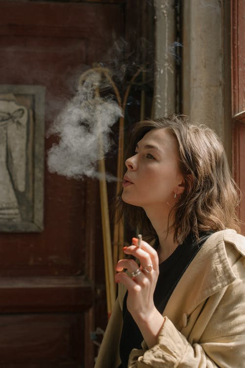 Woman in Beige Coat Smoking