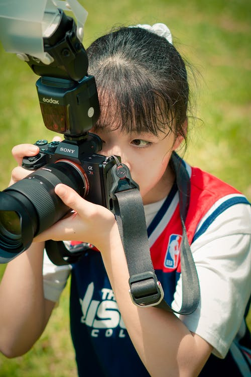 Young female in sportswear with ponytail holding professional photo camera on grassy field