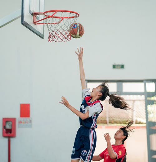 Woman throwing basketball ball in hoop