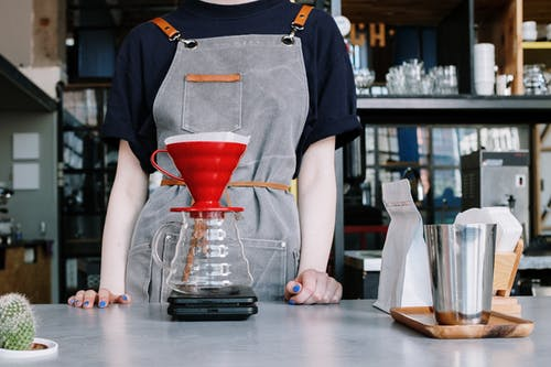 Boy in Blue Crew Neck T-shirt Pouring Red Liquid on Red Ceramic Cup