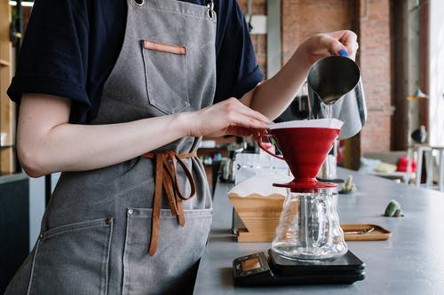 Person in Gray Apron Holding Red Ceramic Bowl