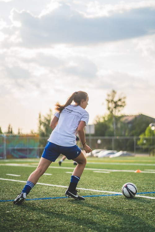 Girl in White Shirt and Blue Shorts Playing Soccer