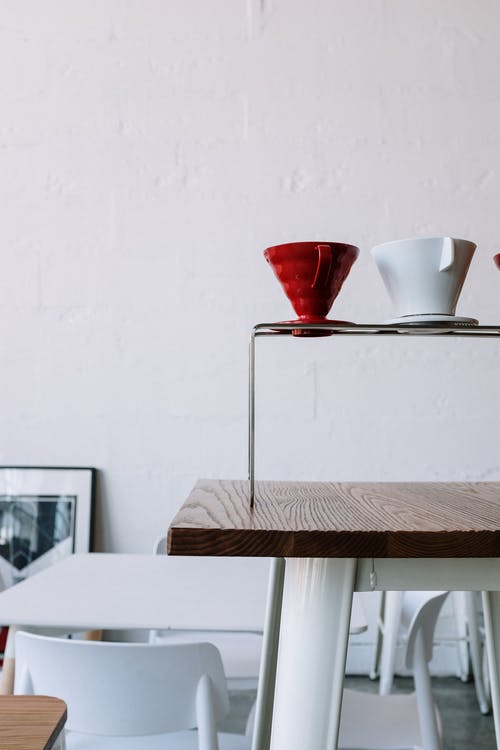 Red and White Ceramic Cup on Brown Wooden Table