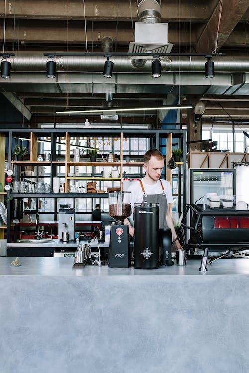 мужчина в серой футболке с круглым вырезом стоит возле черно серебряной кофеварки