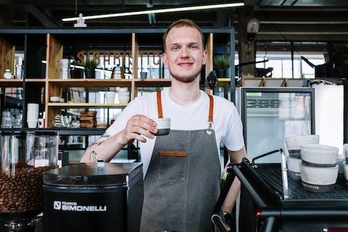 мужчина в серой футболке с круглым вырезом держит черно белый пластиковый стаканчик