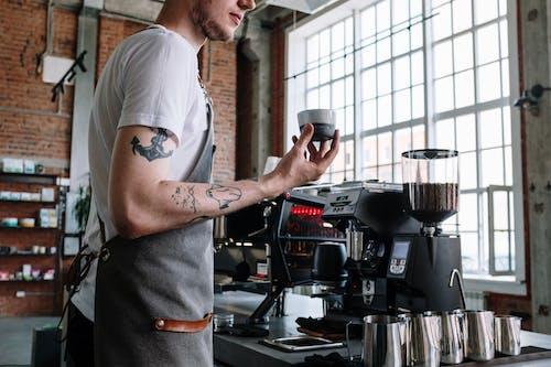 Мужчина в белой футболке наливает кофе на черную кофеварку