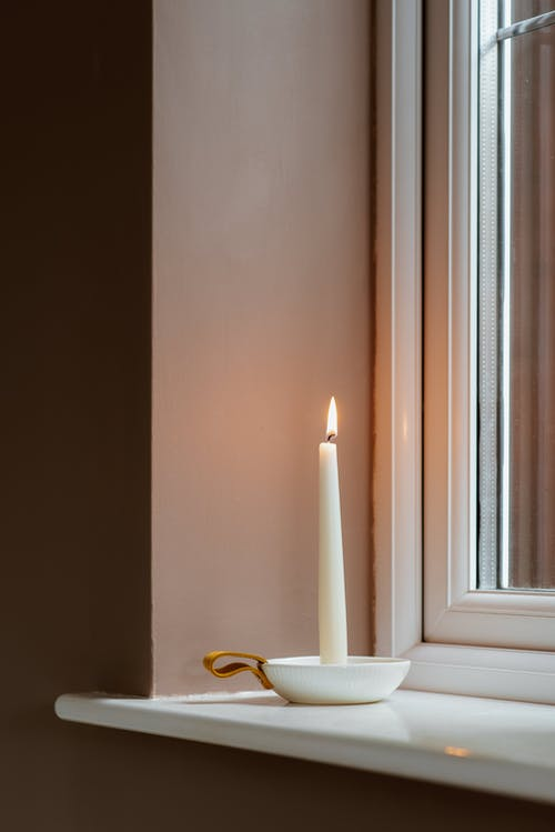 Wax candle with shiny flame in small ceramic bowl near window and house wall