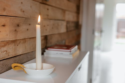 Shiny candle near pile of books and wooden wall