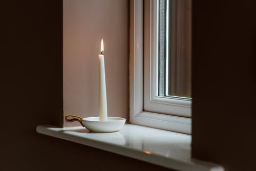 Burning candle in bowl on windowsill in evening