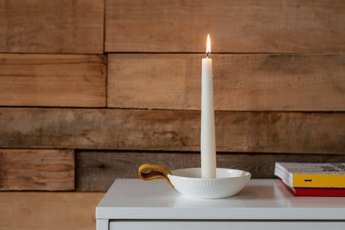 Wax candle with luminous flame in ceramic bowl with clip near textbooks and wooden wall