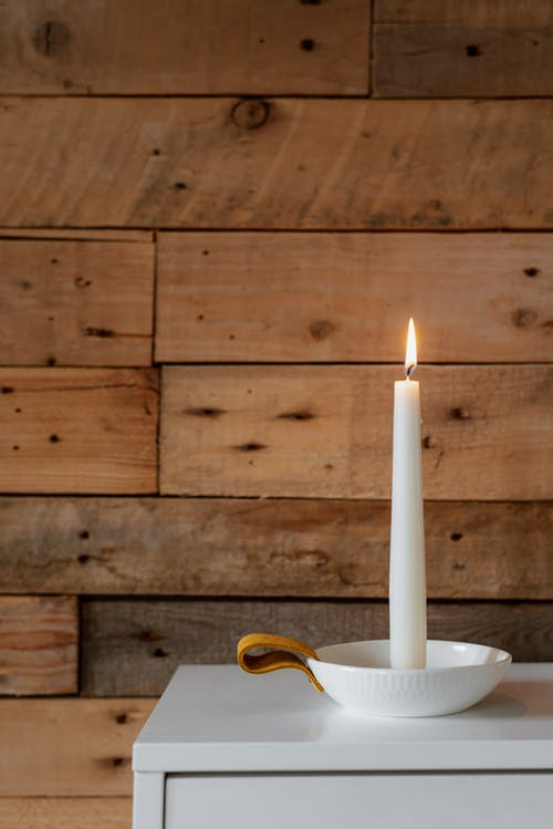 Bright burning candle near wooden wall in house