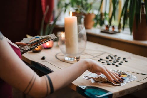 Anonymous soothsayer reading tarot cards during divination process in house