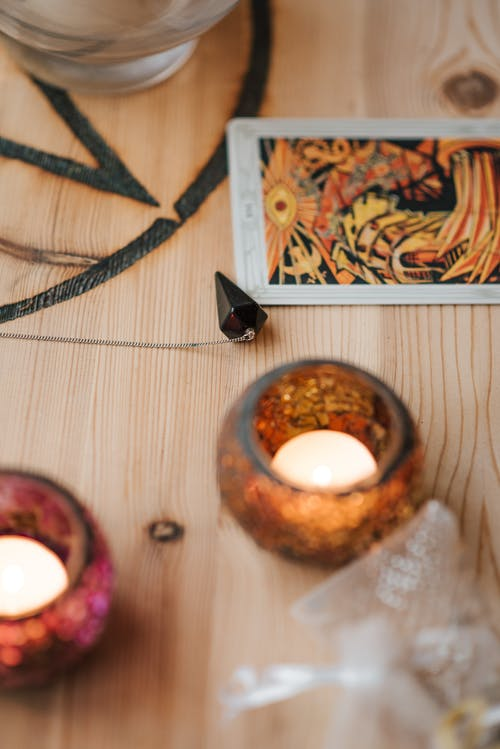Burning candles near tarot card on wooden table