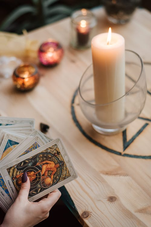 Faceless soothsayer predicting fate with tarot cards