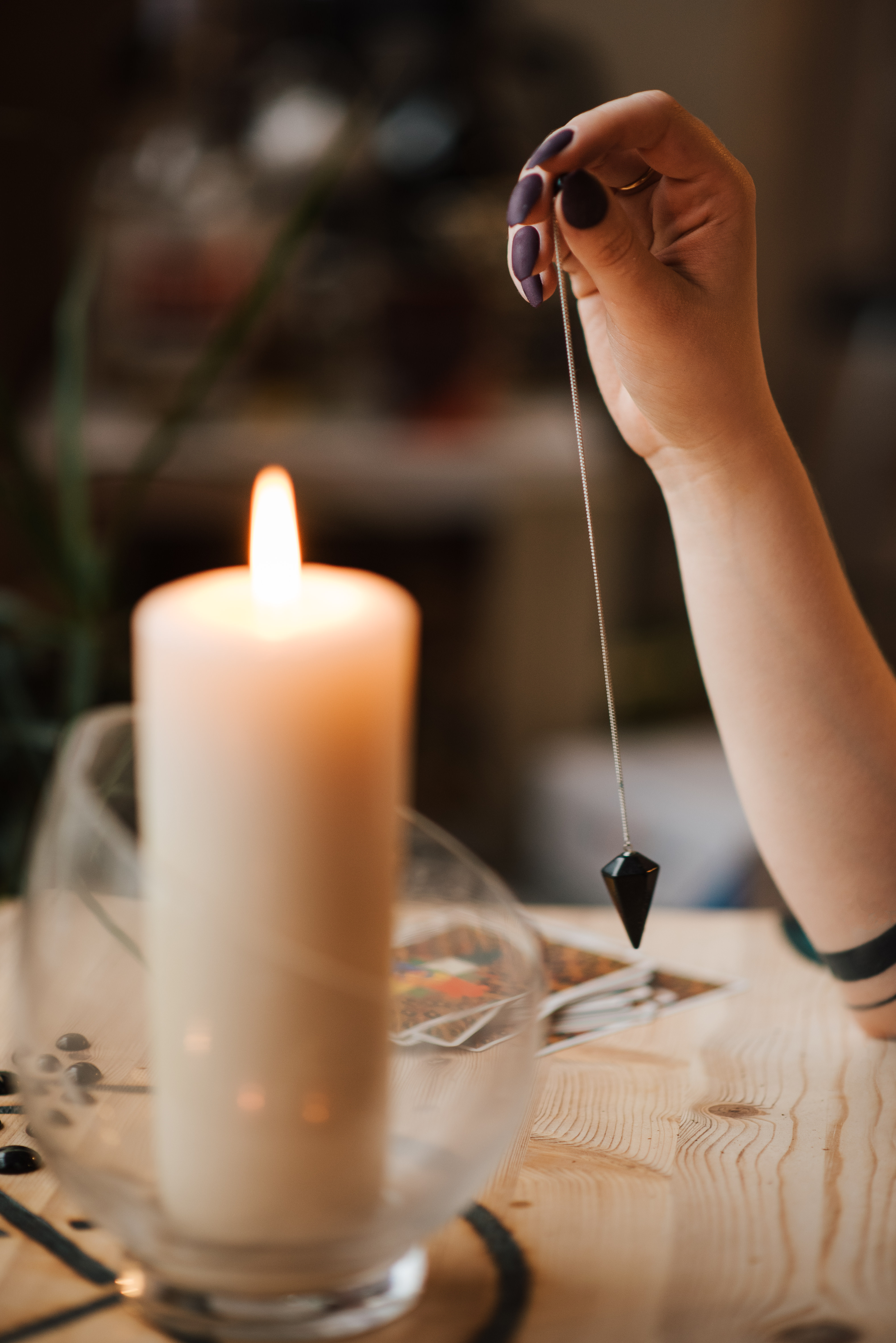 crop fortune teller with amulet near shiny candle