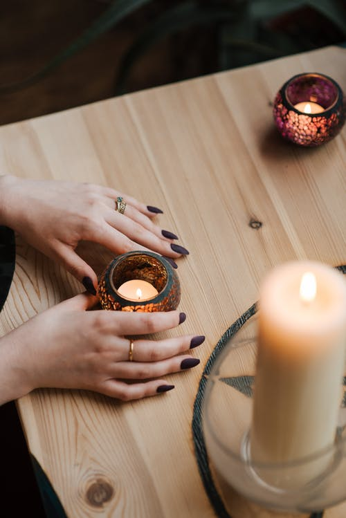 Crop fortune teller with shiny candles at table