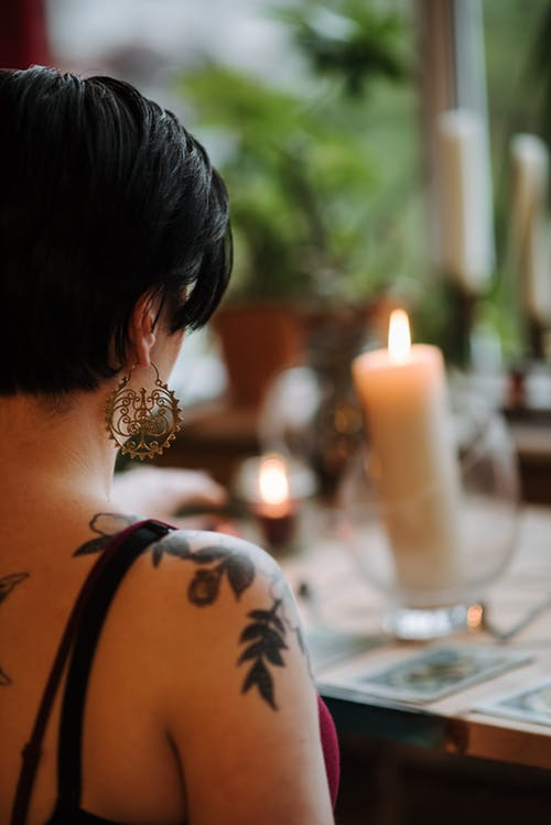 Faceless tattooed fortune teller reading tarot cards at home