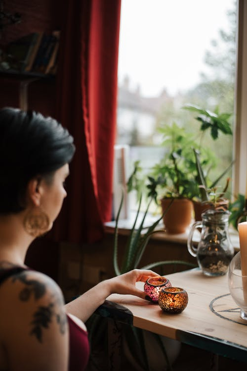 Unrecognizable soothsayer with shiny candles near house window