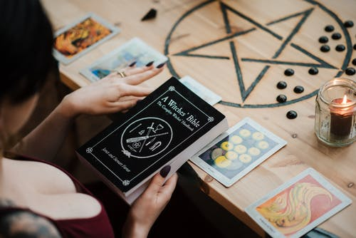 Crop fortune teller with magic book and tarot cards