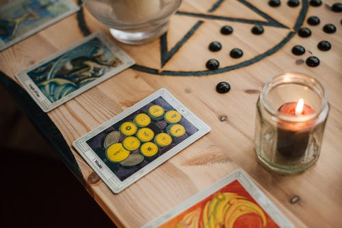 From above of shiny candle in jar near bright tarot cards with illustrations on wooden table with oracle symbol