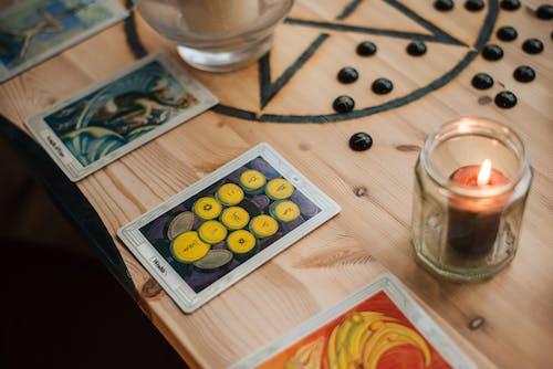 Burning candle near tarot cards on table