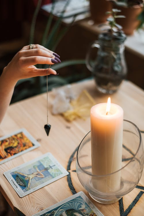 Crop soothsayer with talisman and tarot cards near glowing candle