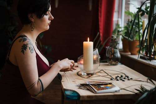 Crop fortune teller predicting fate near burning candle
