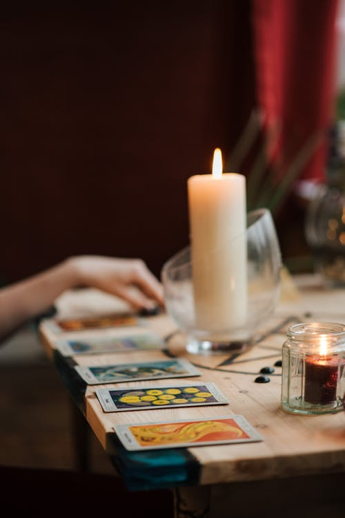 Crop soothsayer reading tarot cards near luminous candles