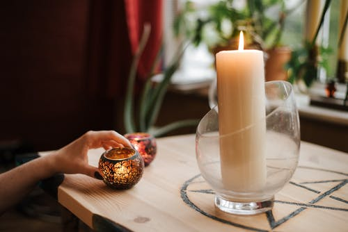 Crop fortune teller near shiny candles at table at home