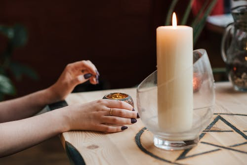 Crop soothsayer predicting fate with burning candle in house