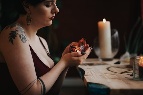 Crop tattooed soothsayer predicting fate with burning candle