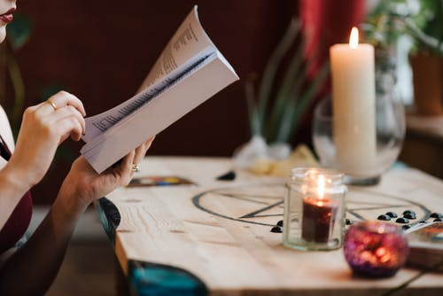 Crop fortune teller reading magic book at table with candles