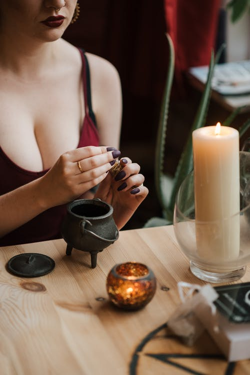 Crop unrecognizable female sorceress preparing mixture in clay teapot near glowing candles at home