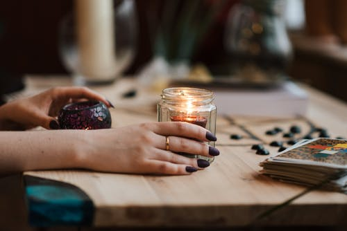 Faceless fortune teller with burning candles at home
