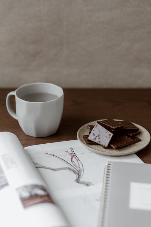 Opened magazine near plate with delicious chocolate and mug with water on wooden table