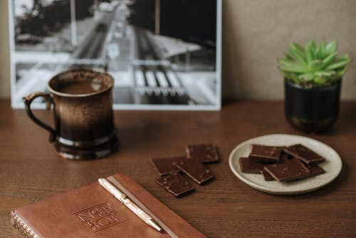 High angle of notebook with leather cover near milk chocolate and cup of fresh aromatic coffee on wooden table