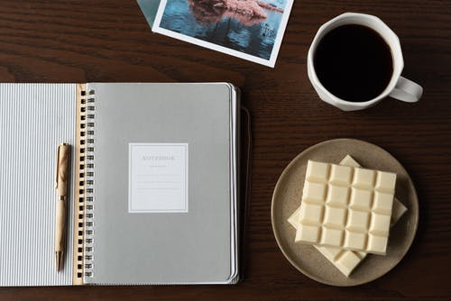 Notebook near coffee and white chocolate