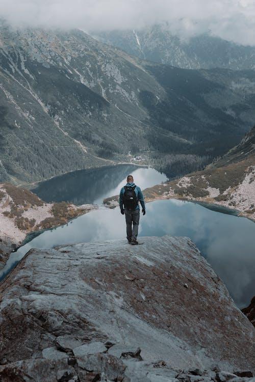 Man Standing on a Mountain near a Lake