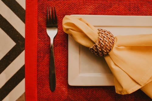 Top view composition of napkin in holder placed on ceramic table near fork on red place mat in banquet hall