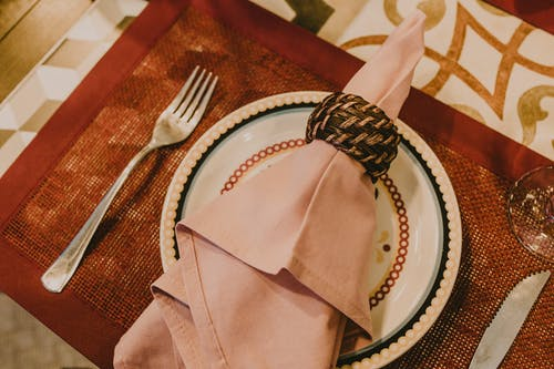 From above layout of table setting with pink napkin served on fancy ceramic plate on place mat near cutlery