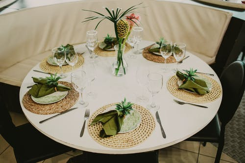 High angle round dining table served with dinnerware with green napkins and wineglasses arranged around decorative plant in vase