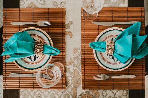 Top view stylish arrangement of ornamental plates with blue napkins served on place mat on table near wineglasses
