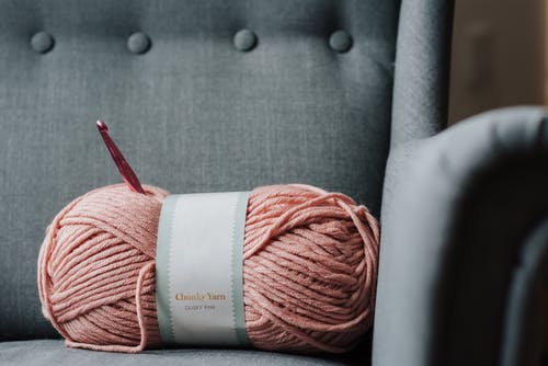 Pink yarn for knitting on sofa