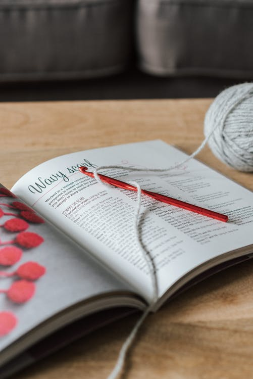 High angle of gray yarn ball with crochet hook and craft magazine on wooden table at home