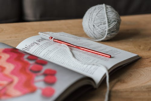 Spherical gray ball of thread and red crochet needle with magazine on beige wooden table in daytime on blurred background